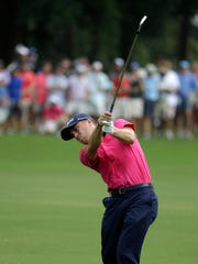 Justin Thomas hits from the rough on the ninth hole