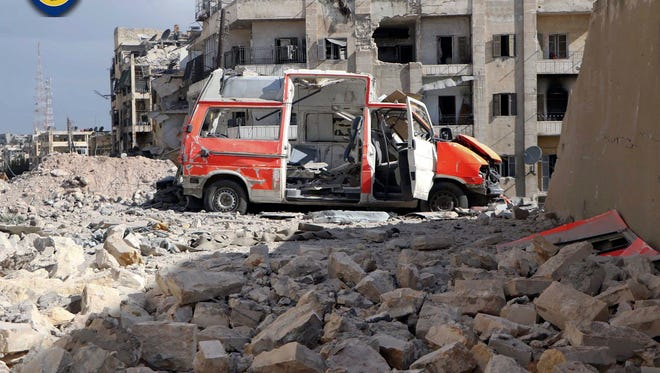 FILE - In this photo provided by the Syrian Civil Defense group known as the White Helmets, taken Sept. 23, 2016, a destroyed ambulance is seen outside the Syrian Civil Defense main center after airstrikes in Ansari neighborhood in the rebel-held part of eastern Aleppo, Syria.