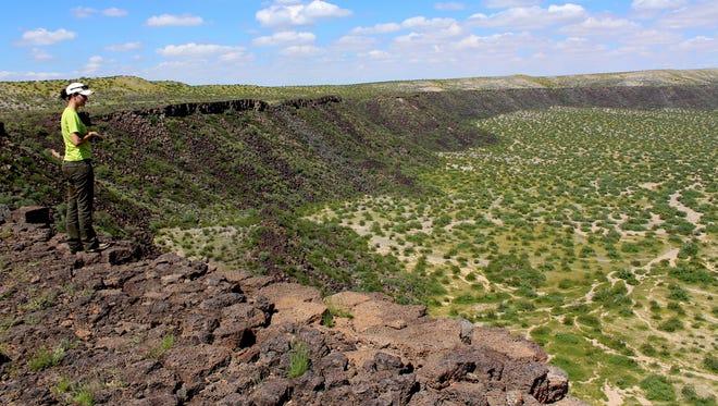 A visitor to Kilbourne Hole Volcanic Crater National Natural Landmark surveys the geological formation.