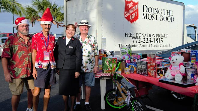 The Treasure Coast Parrot Head Club collected toys and donations for the Salvation Army of Martin County's Angel Tree program at its annual Christmas in the Caribbean party. From left are club President Tom Edwards, Don Pendagast, Salvation Army Capt. Christine Kim and Joe Howe.