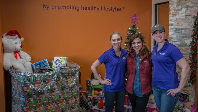 Ashley Caviness from Anytime Fitness, from left, Tenille Rauls of The CALL of Baxter County and Malinda Steen, also of Anytime Fitness, recently hosted the Anytime Fitness Christmas Bash Toy Drive. The gym partnered with The CALL  along with local businesses to collect toys for foster children.