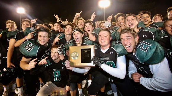 Yorktown celebrates with the plaque after defeating Somers 21-7 in the Section 1 Class A championship football game at Mahopac High School on Friday, November 3rd, 2017.