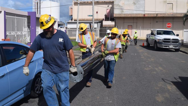 Workers from Richmond Power & Light and other electric utilities carry a new pole to install on the island of Puerto Rico.
