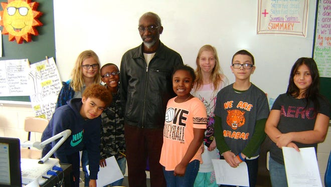 Roosevelt Manns stands with some of the fifth-graders at Malabar Intermediate School who asked him questions Friday about racial segregation in the South.