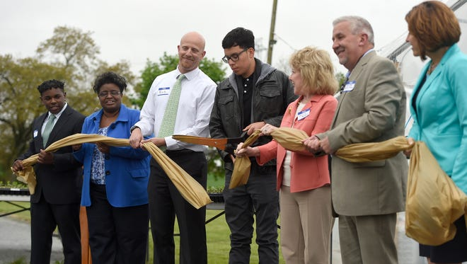 Dignitaries and guests attended a ribbon cutting of a commercial-sized greenhouse at the Youth Advocate Program, 1691 Grace Ave., that will be tended by members of the Youth Advocate Program, which is a counseling program for juvenile offenders. It was funded by a Family and Children's Services Grant through the Foundation for Enhancing Communities, Wal-Mart and by Ed and Jeanne Arnold. Frankie Ramos, holding scissors, cuts the ribbon May 4, ceremoniously opening the greenhouse.