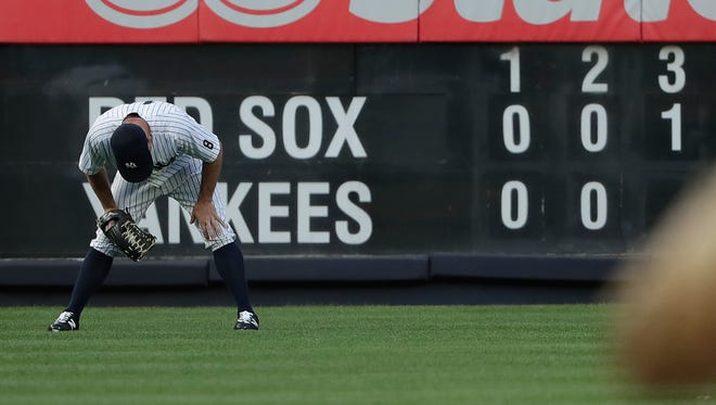 New York Yankees left fielder Brett Gardner pauses before the next batter after a solo home run by Boston Red Sox's Ryan Hanigan during the third inning of a baseball game Friday, July 15, 2016, in New York.