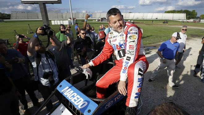 FILE -- Tony Stewart climbs into Carson Macedo's midget race car to do a couple laps on the 3/16th oval made for him inside turn three of the Indianapolis Motor Speedway.