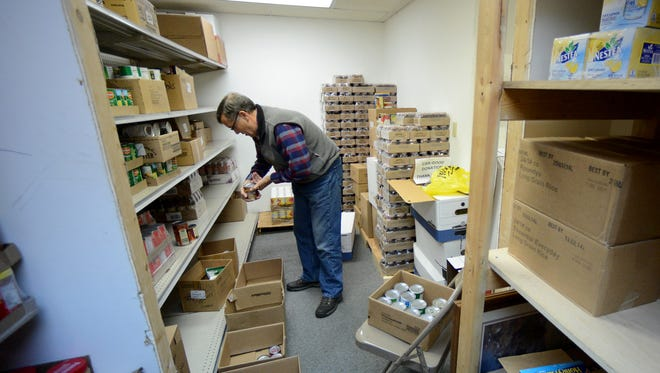 Volunteer Larry Peterson sorts food at the Resurrection Lutheran Church Food Pantry in Green Bay.
