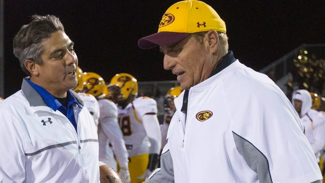 Chandler head coach Shaun Aguano shakes hands with Mountain Pointe head coach Norris Vaughan after Chandler defeated Mountain Pointe in the  Division I High School football semifinals at Hamilton High on Nov. 21, 2014.