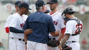 Boston's Xander Bogaerts, left, and Blake Swihart (23) listen as pitching coach Carl Willis, center, talks with Rick Porcello during a mound visit in the first inning of a spring training game Monday. (AP Photo/Tony Gutierrez)