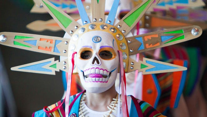 A child wears an intricate mask just before the procession starts at the El Puente Theatre Festival and Mask Procession, September 21, 2014, in Tempe, Ariz.