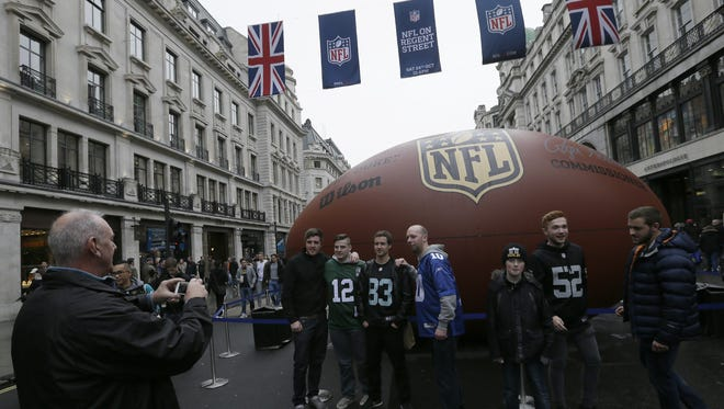 Football fans pose for pictures during an NFL fan rally on Regent Street in London.