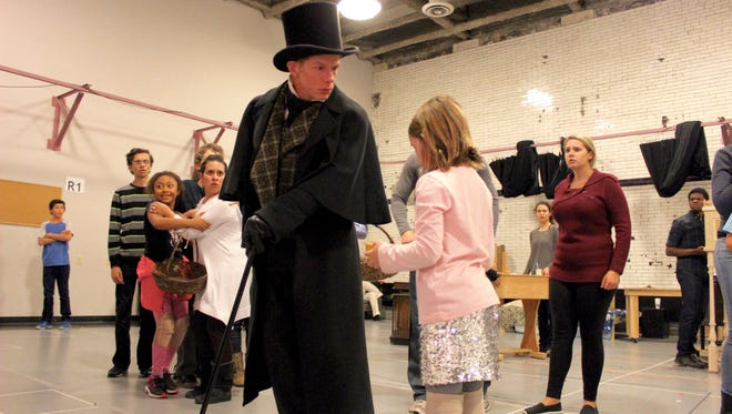 "As Scrooge, Jonathan Wainwright rehearses a scene with younger members of the ""Christmas Carol"" cast."