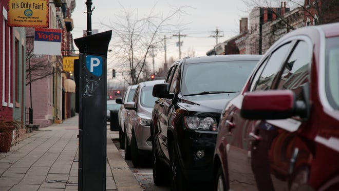 Cars are parked along Main Street near a parking kiosk, Friday, Jan. 13, 2017, in Covington, Ky.