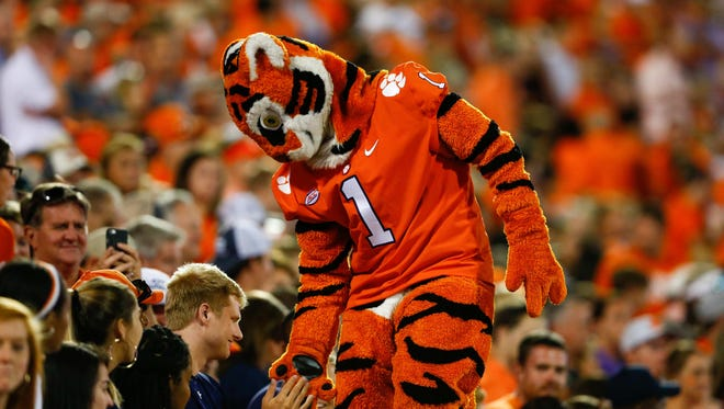 The Clemson Tigers mascot high fives fans during the fourth quarter against the Auburn Tigers at Clemson Memorial Stadium.