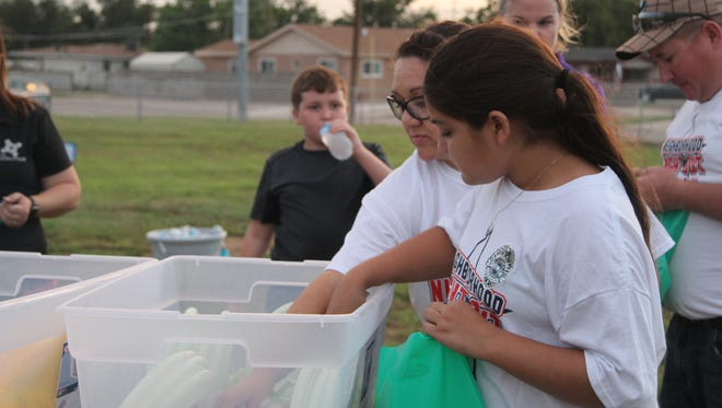 Eleven-year-old Marissa Estrada picks through a bucket of free items Carlsbad Anti-Drug/Gang Coalition's National Night Out event, Tuesday, Oct. 3, 2017. Marissa and several other students also volunteered at the event,