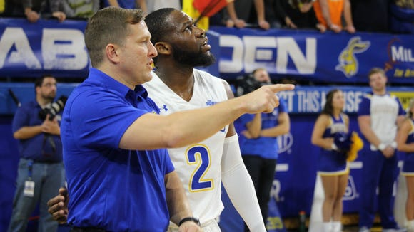 TJ Otzelberger discusses strategy with Tevin King at a game earlier this season.