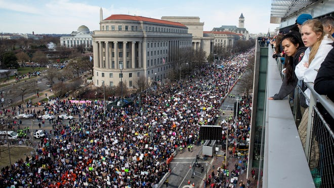 Young people visiting the Newseum look out upon thousands of people gathered for March For Our Lives on Pennsylvania Avenue in Washington, DC on March 24,  2018.