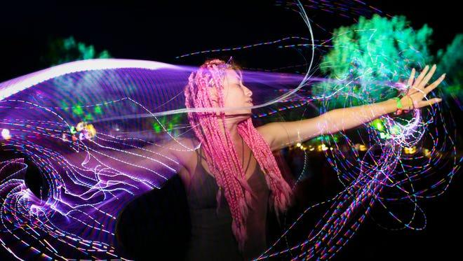 Natalia Burgos uses a fiber optic whip to dance at Bonnaroo on Thursday evening. June 7, 2018