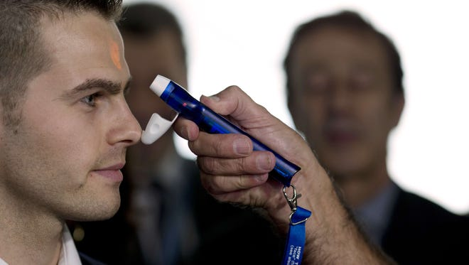 An employee of the airport emergency medical service uses an electronic thermometer to gauge temperatures in the fight against Ebola virus on Oct. 17, 2014, at the Roissy-Charles-de-Gaulle airport in Roissy-en-France, a suburb of Paris, before carrying out health checks on travelers arriving from Guinea, one of the worst-hit nations alongside Liberia and Sierra Leone.