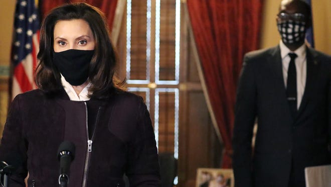 """In this photo provided by the Michigan Office of the Governor, Gov. Gretchen Whitmer addresses the state during a speech in Lansing, Mich., Thursday, Dec. 3, 2020. The governor said her administration may extend portions of a three-week partial shutdown of schools and businesses next week because of the """"sheer volume"""" of coronavirus cases around Michigan. She said no decision had been made but added the while curve has leveled, it ultimately must come down to ensure hospitals are not overrun."""