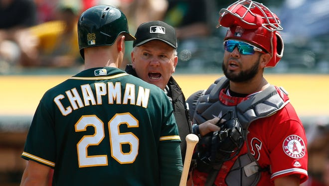 Oakland Athletics third baseman Matt Chapman and Los Angeles Angels catcher Juan Graterol  exchange words in front of umpire Mike Everitt in the fourth inning at Oakland Coliseum.