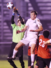 East Kentwood goalie Haris Dzafic (left) punches the