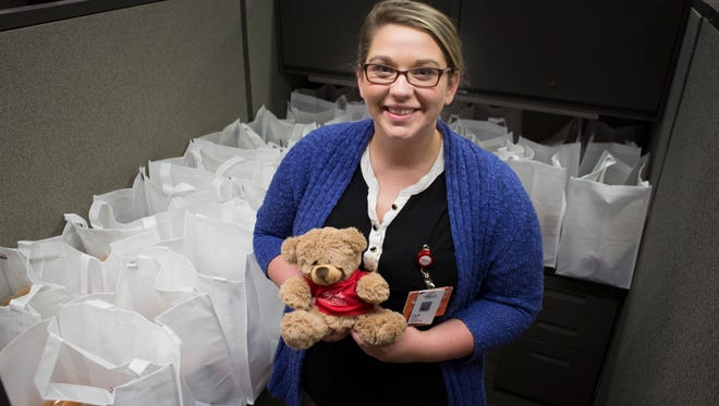 Lila Bradley, a marketing intern at Augusta Health, stands next to a few of the 100 baby shower gift bags she has helped assemble for the medical center's Babypalooza event that will be taking place Saturday at the Waynesboro Best Western conference center.