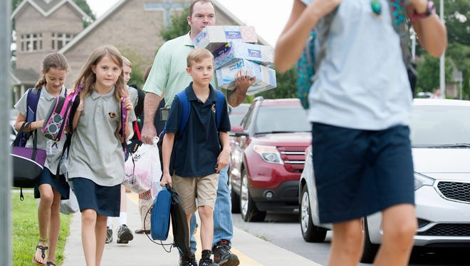Students and parents walk into school for the first day at Charles T. Koontz Intermediate School on Aug. 19, 2015. A new uniform policy was implemented for the first time that year.