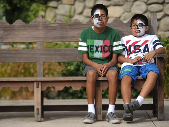 Christian Cuahutl, left, and his brother Angel, of Oxnard, wait for the next group to perform during a Dia de los Muertos celebration at the Museum of Ventura County two years ago.