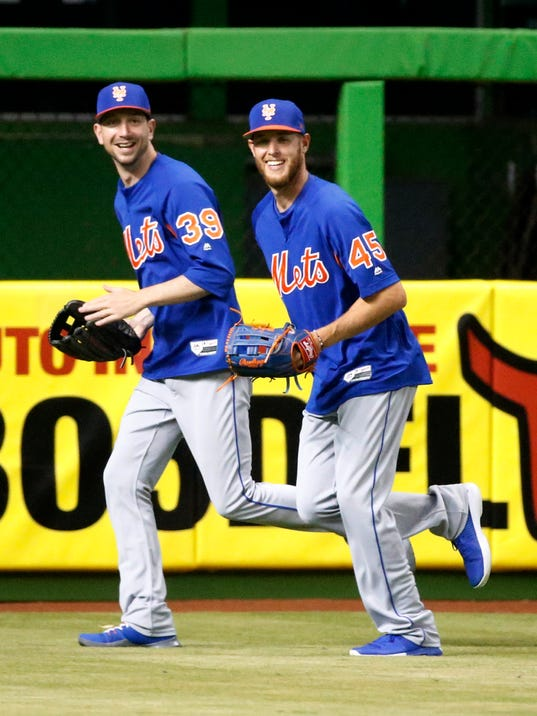 New York Mets pitchers Zack Wheeler (45) and Jerry Blevins (39) chat as they field balls during batting practice for the team's baseball game against the Miami Marlins, Tuesday, April 10, 2018, in Miami. Wheeler is scheduled to make his first start of the year Wednesday against Miami as the last piece of a rotation expected to be one of baseball's best. (AP Photo/Wilfredo Lee)