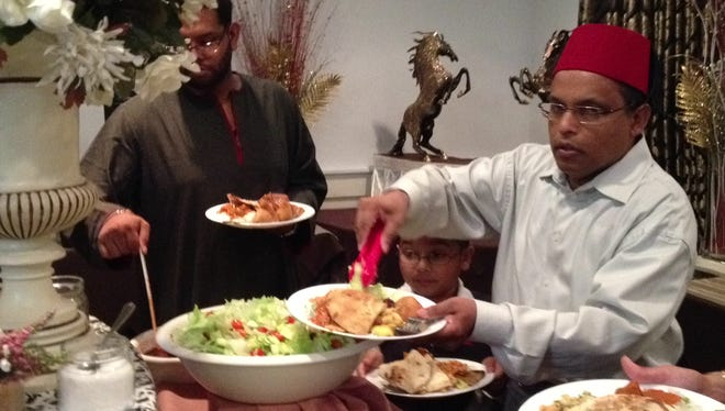 Belayat Choudhury pf the Belle Mead section of Montgomery serves his 8-year-old son, Jaffrey, during an Islamic Relief fundraiser on Thursday at Shahnawaz Palace in Edison.