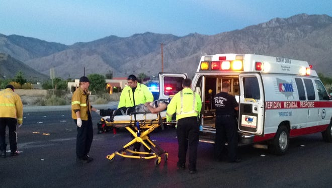 Paramedics load a man who was hit by a car along Ramon Road in Palm Springs into an ambulance on Aug. 26, 2014.