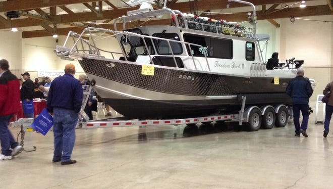 Guests look at a fishing boat exhibit at the Saltwater Sportsmen's Show on Saturday.
