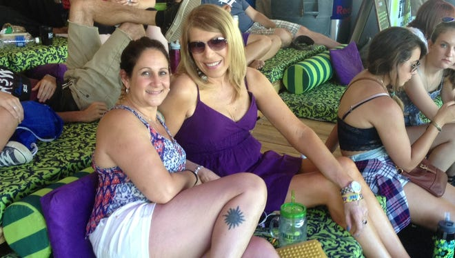 Lisa Deorio (left) and her friend, Kathy Bozinski, both 51, recline in the VIP tent by Firefly's Main Stage