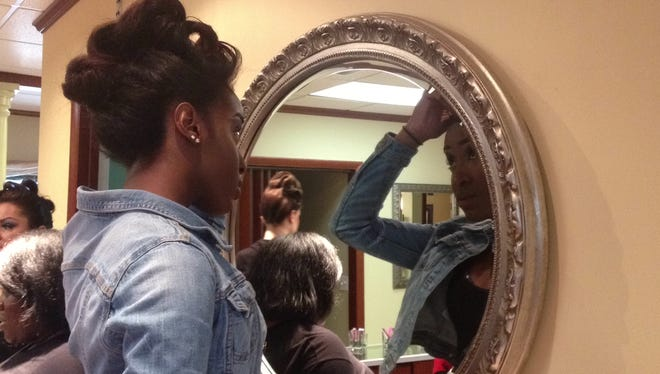 Bear resident and former Miss Delaware contestant Keturah Braithwaite, 18, touches up her look in the mirror.