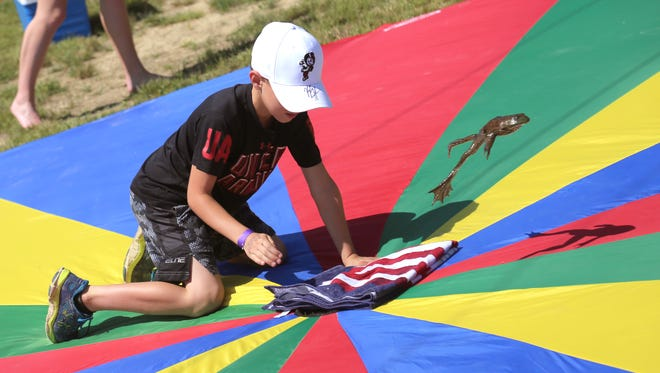 Tyler Turnbagh, 8, gets his frog to jump during the annual Lions Club Fourth of July Frog Jump at Ontario Middle School on Saturday.