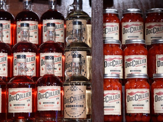 Varieties of moonshine are displayed on shelves at