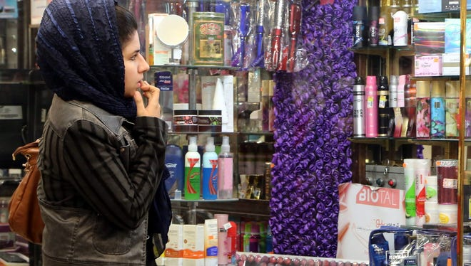An Iranian woman window shops at a cosmetic shop in Tehran, Iran, Nov. 25, 2013.