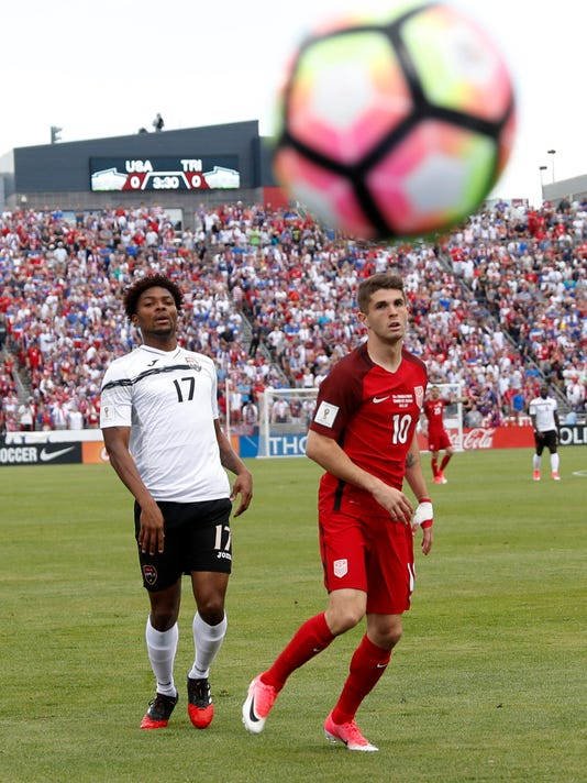 U.S. midfielder Christian Pulisic, right, watches his shot bound out of play, next to Trinidad & Tobago defender Mekell Williams during the first half of a World Cup soccer qualifying match Thursday, June 8, 2017, in Commerce City, Colo. (AP Photo/David Zalubowski)