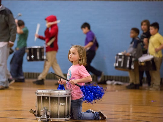 Ella Miller, 6, plays the drums in the middle of the gym floor as other members of the Boom Squad circle around playing during their practice on Tuesday evening.