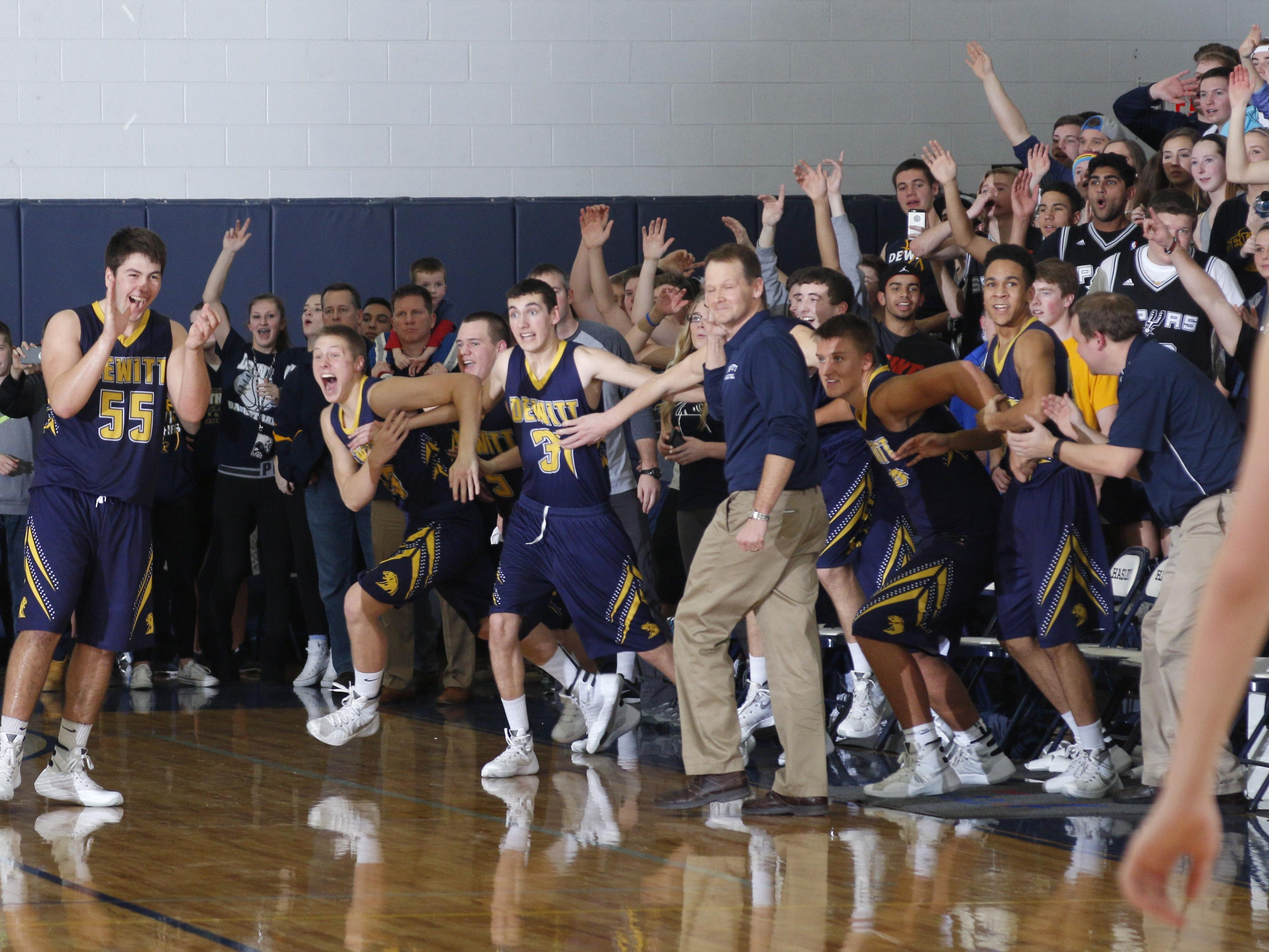 DeWitt players, the bench and fans celebrate as time expires in a 77-72 overtime win over Haslett Friday, Jan. 15, 2016, in Haslett, Mich.
