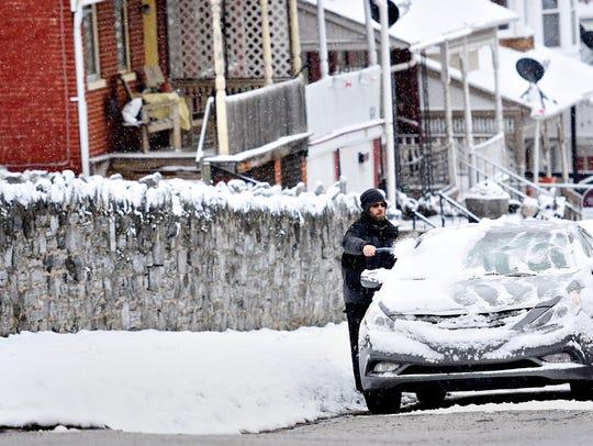 Damion Kamarauskas, of York City, brushes the snow