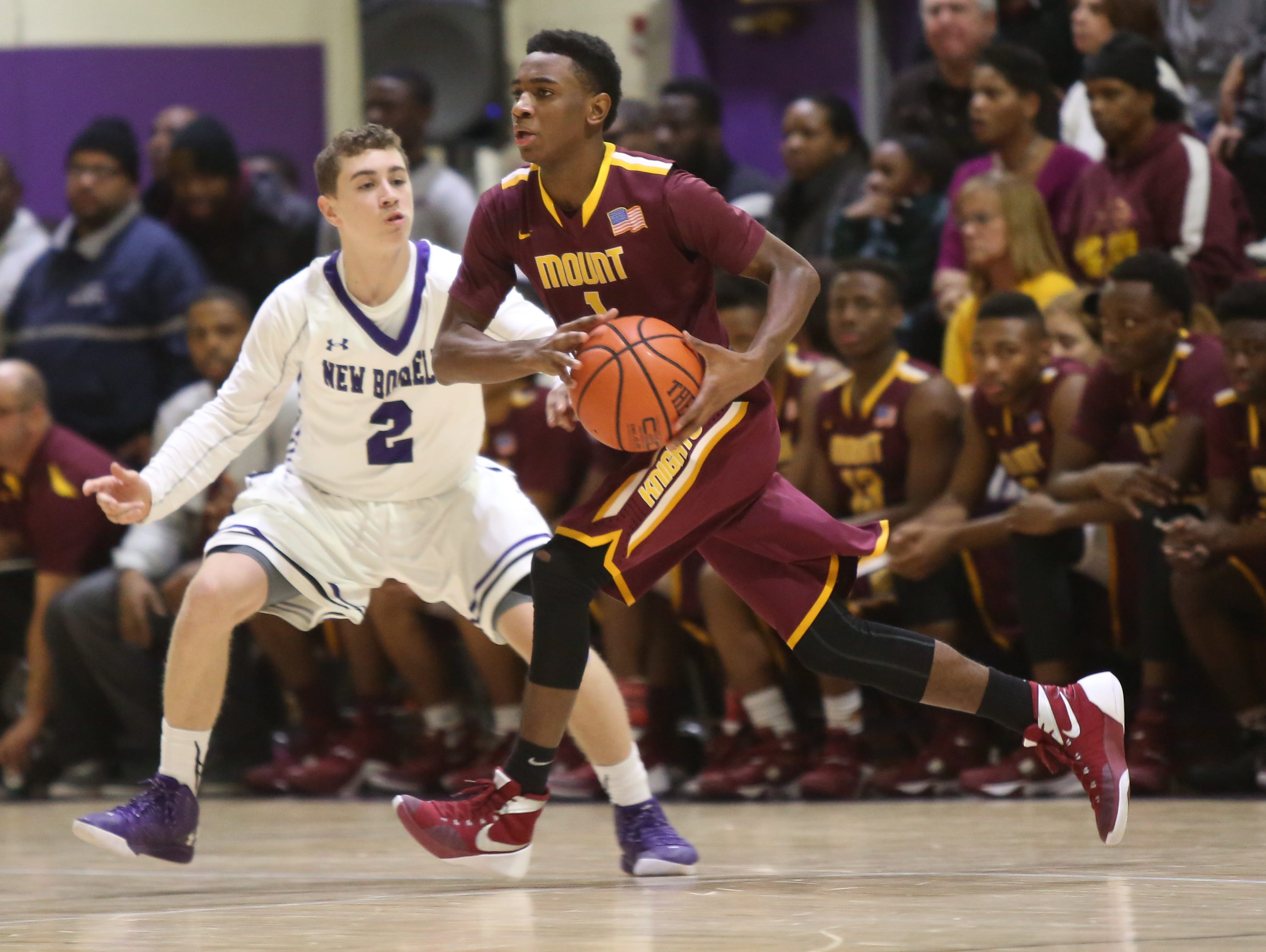 Jared Young (1) of Mount Vernon dribbles pass Jake Mieto (2) of New Rochelle during game action at New Rochelle High School on Jan 4, 2016. Mount Vernon defeated New Rochelle 72-63.