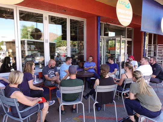 The staff at La Grande Orange Grocery and Pizzeria takes a break from cleaning and renovating the Arcadia landmark to have a staff meeting on the sidewalk out front.