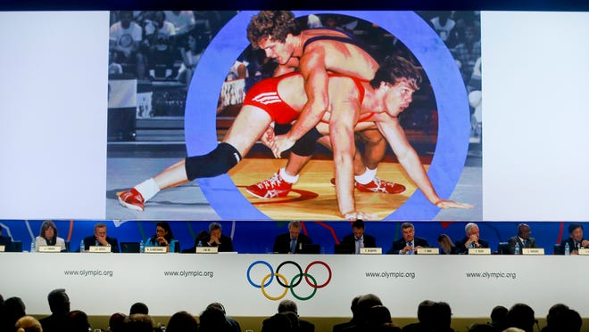 International Olympic Committee members watch a wrestling presentation video  during the 125th IOC session in Buenos Aires, Argentina,  Sunday.
