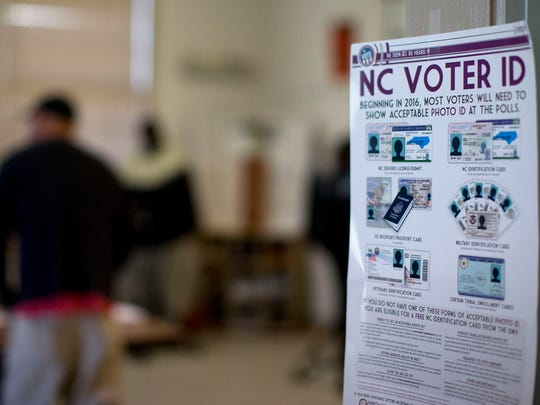 North Carolina's new voter ID rules are posted at the door of a voting station in Greensboro during the state's March primary.