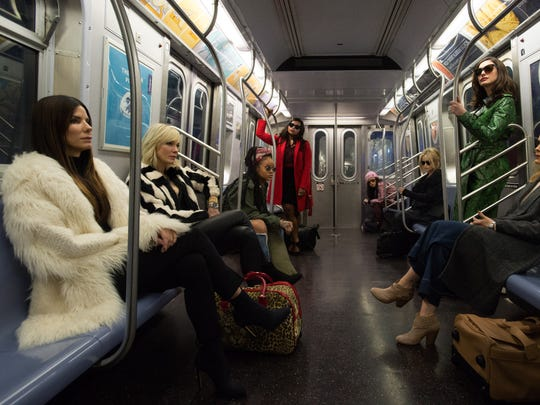 Sandra Bullock (left, seated) leads the crew in 'Ocean's 8.'
