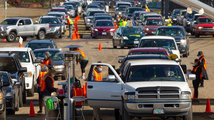 Cars full of people wanting a COVID-19 vaccine line up in the parking lot of Autzen Stadium in Eugene, Oregon, on March 27, 2021.