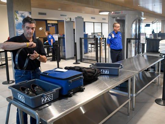 Air passenger Rick Buffalini prepares his belongings